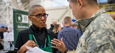 Starbucks partner at a job fair talking with a person in military camouflage