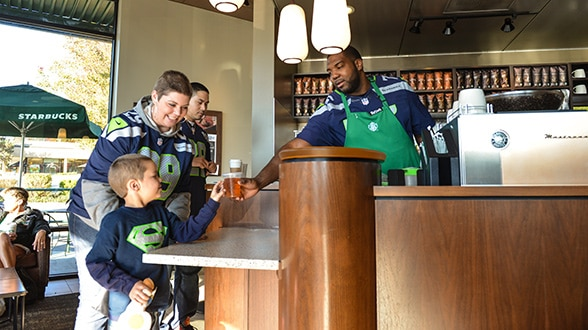 Guest barista Russell Okung hands a young fan his beverage.