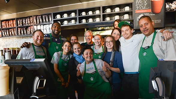 Coach Pete Carroll, Russell Okung, and Blair Taylor, Starbucks chief community officer, with the team from I-405 & 44th in Renton.