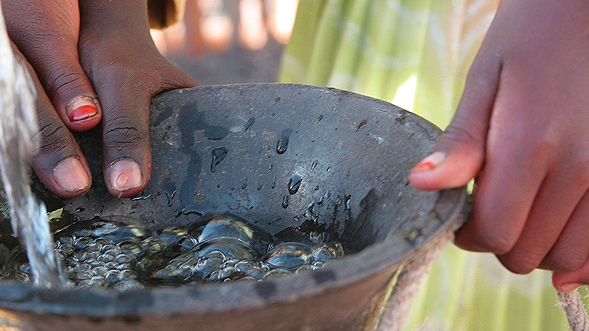 Hands collecting clean water in a vessel