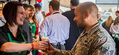 Starbucks barista handing a drink to a person in military camouflage